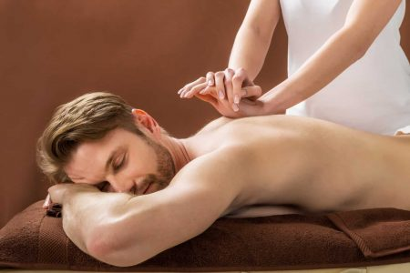 Portrait Of A Young Man Receiving Back Massage At A Beauty Spa